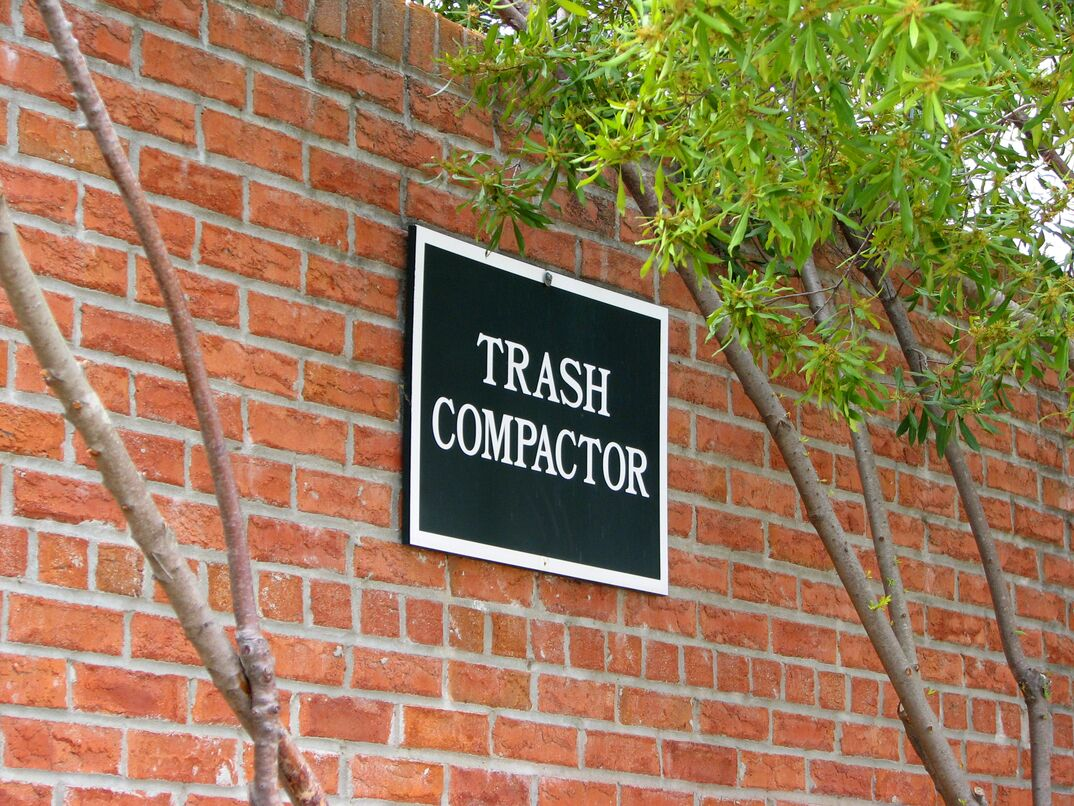 A red brick exterior of a building showing a sign that reads 'trash compactor.'