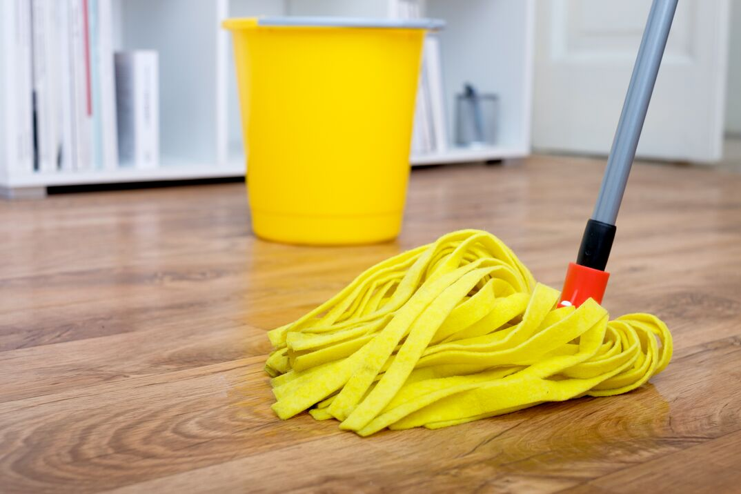 mop and bucket of water sit on a hardwood laminate floor awaiting mopping