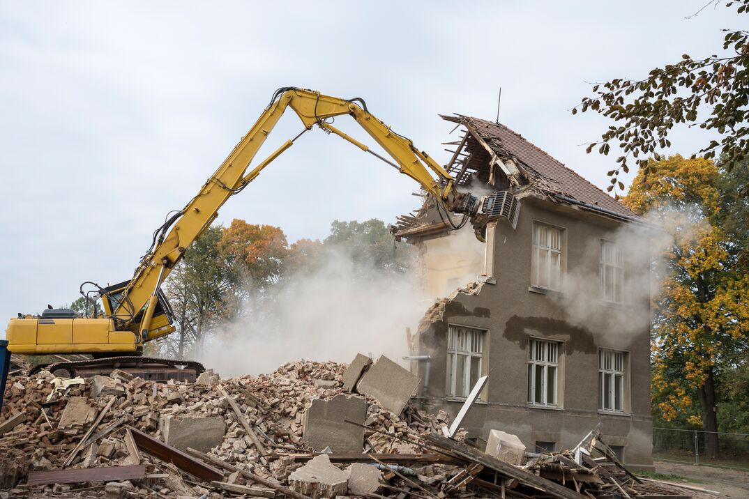 a large CAT excavator is used to demolish an old home