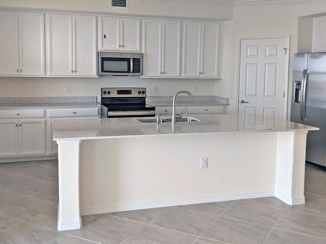 Residential kitchen with white quartz counter tops