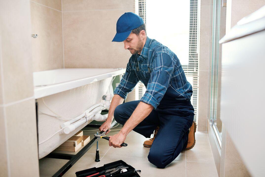 a male technician preparing to level a newly installed bathtub