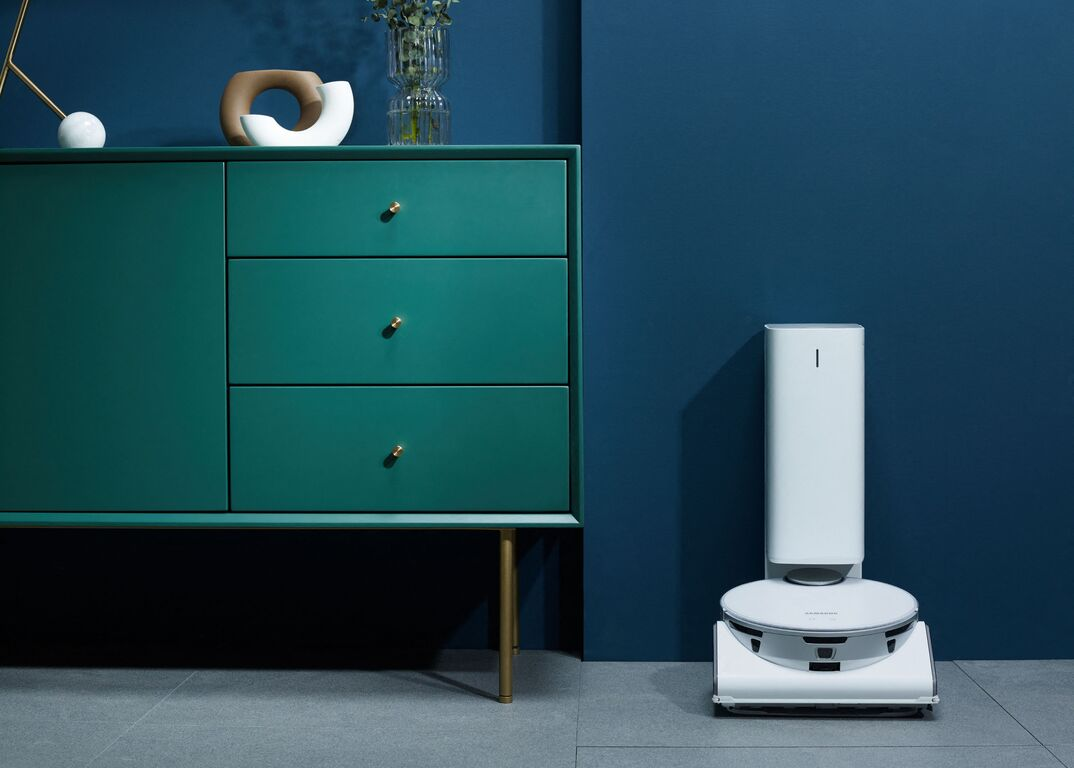 Samsung JetBot 90 AI Plus smart mop docked next to a green dresser with multiple drawers and knickknacks in a room with blue walls.