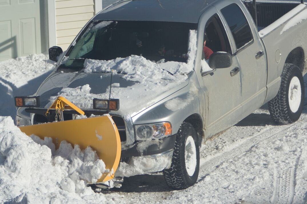 Pickup truck plowing snow in front of house