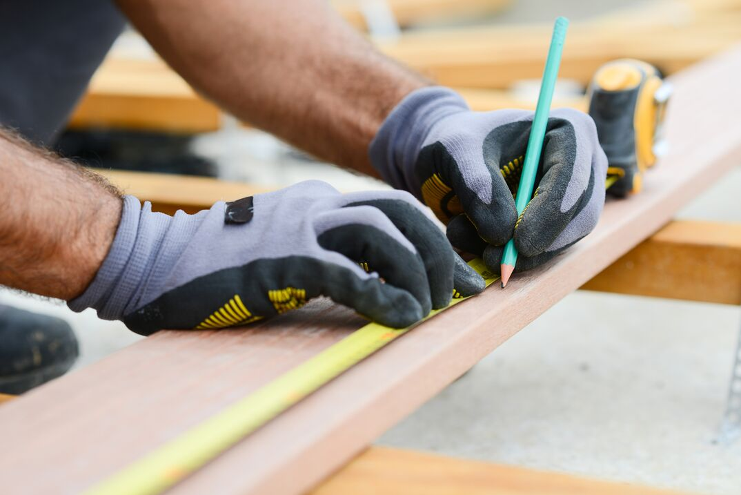 close up detail of manual worker hands working with a measuring tape and pencil in wood plank
