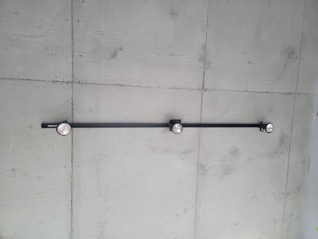 Black metal lighting track with three round spotlight-style lights pointing downward from gray exposed concrete ceiling