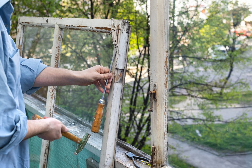Male hands repairing old wooden windows using a hammer and a screwdriver  Repairing interior of old house  Close-up of home DIY project