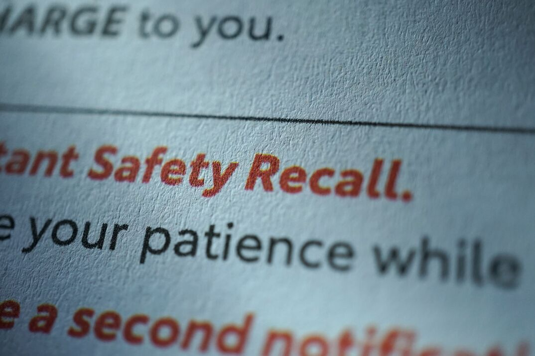 image shows an extream close up of text from a book or magazine that has black text and the words Safety Recall in red text