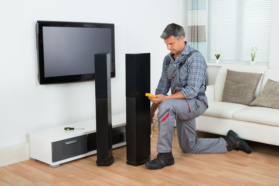 Technician Checking TV Speaker With Multimeter