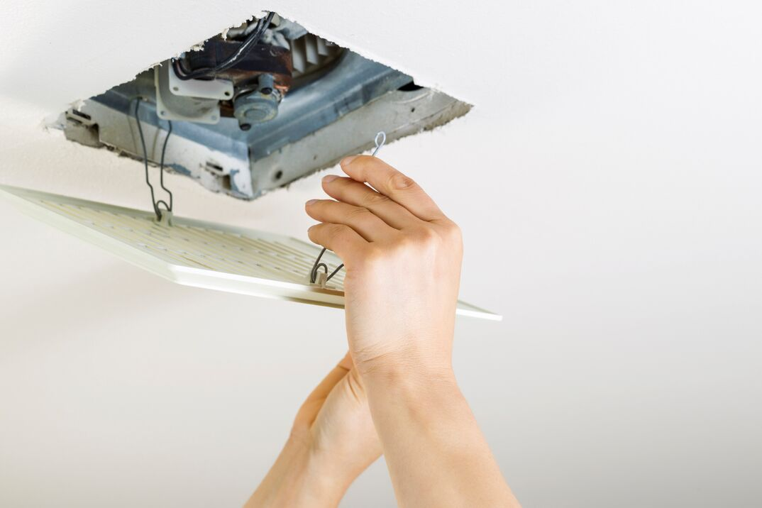 Close up of female hands installing clean bathroom fan vent cover from ceiling
