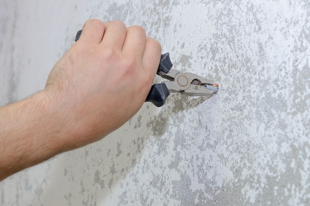 worker with pliers pulls the plug out of the wall