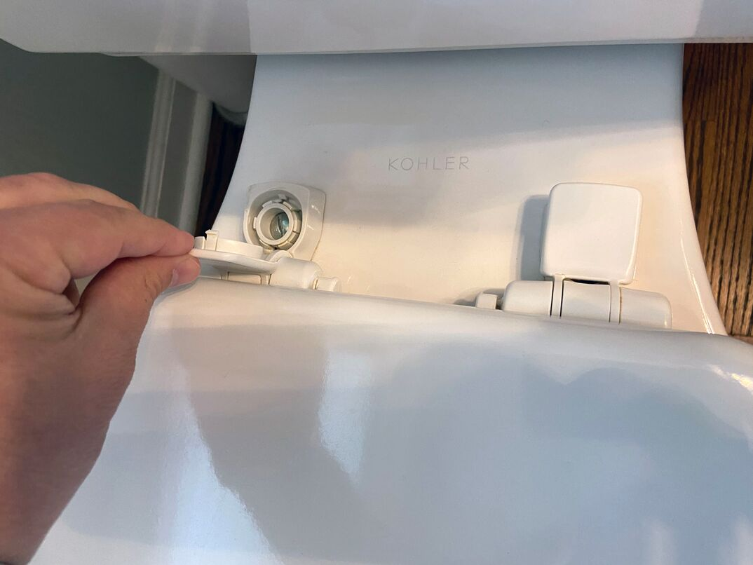 a step-by-step instructional guide to replacing a toilet seat  In a residential home with hardwood floors