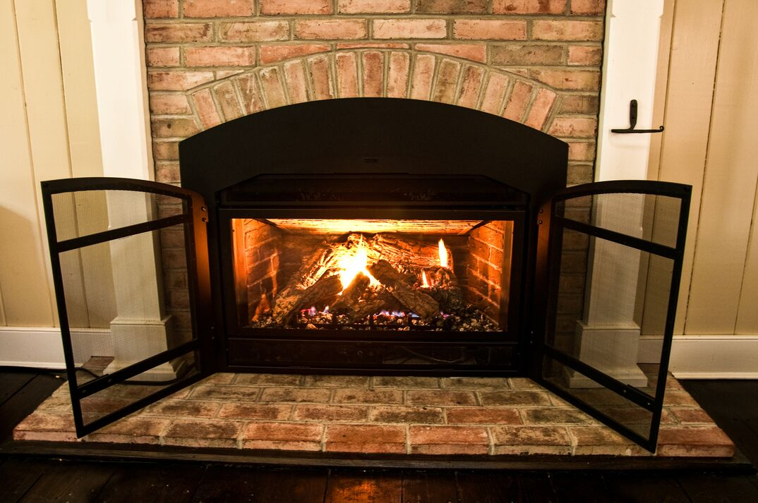Natural gas fireplace with protective screen and surrounded by brick