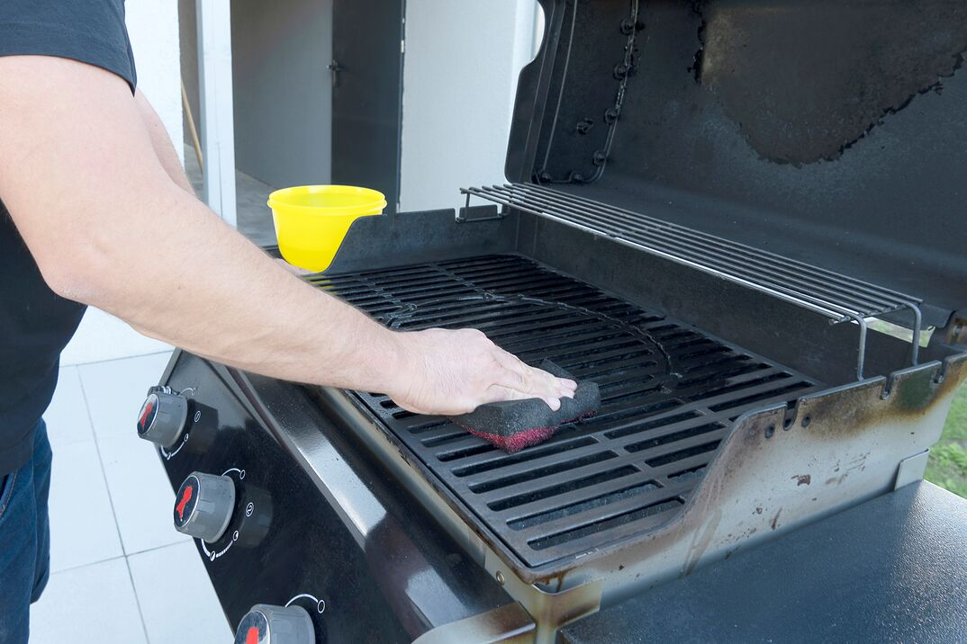 a male s hand cleans a black BBQ grill with a soft brush