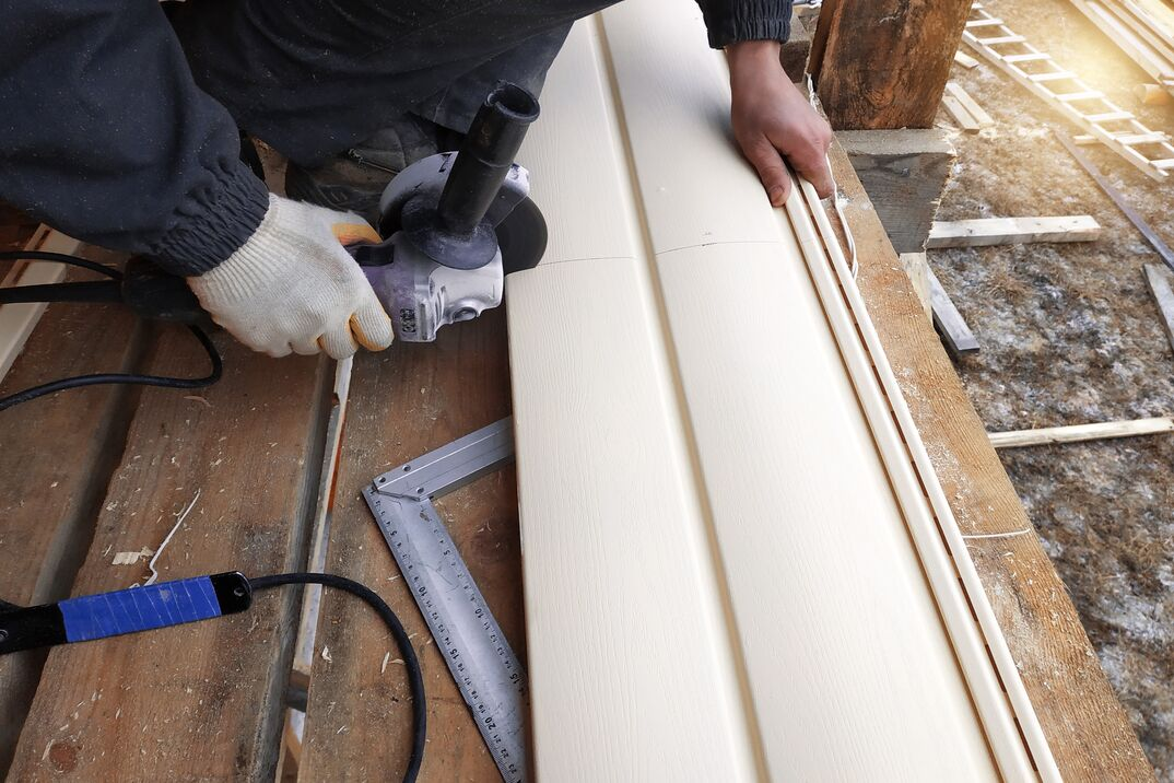 A contractor cuts vinyl siding using a power grinder