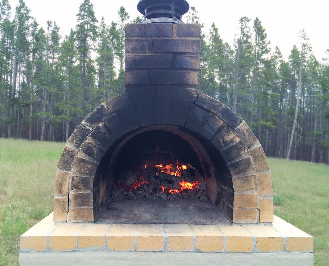 Outdoor Brick Oven In A Grass Clearing Of A Tree Lined Forest