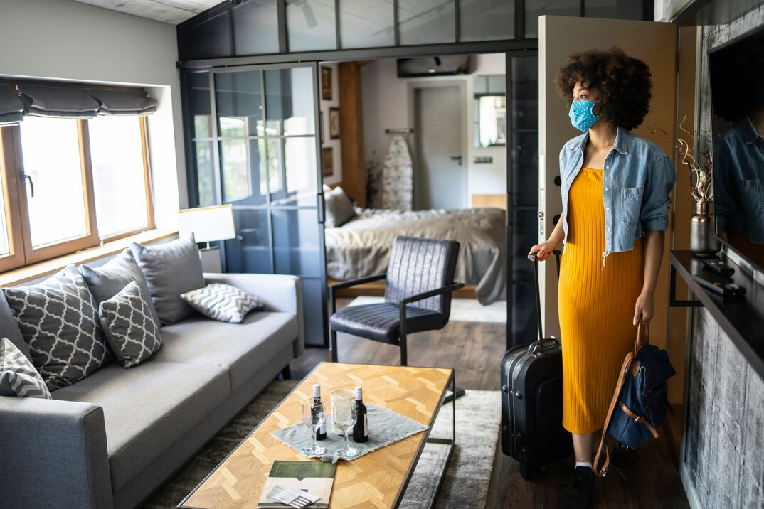 Woman arriving to vacation rental with suitcase