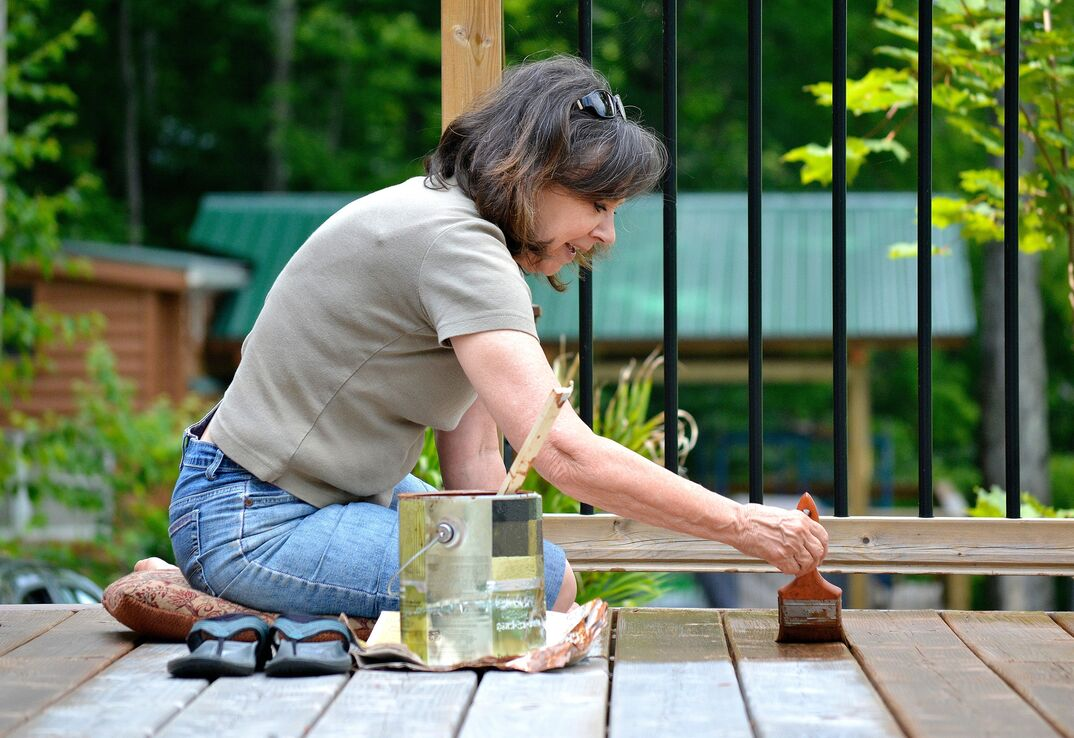 woman applying stain to exterior deck