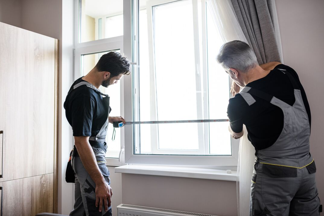 Two contractors measuring a white vinyl window for replacement