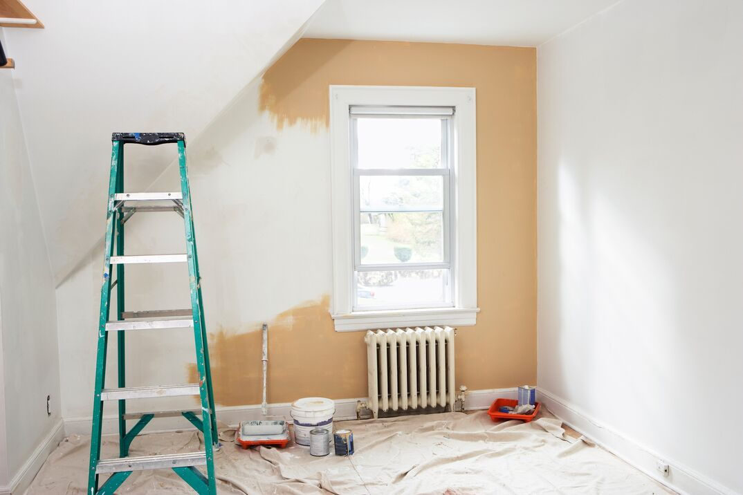 small room with tan paint getting a new coat of white paint applied