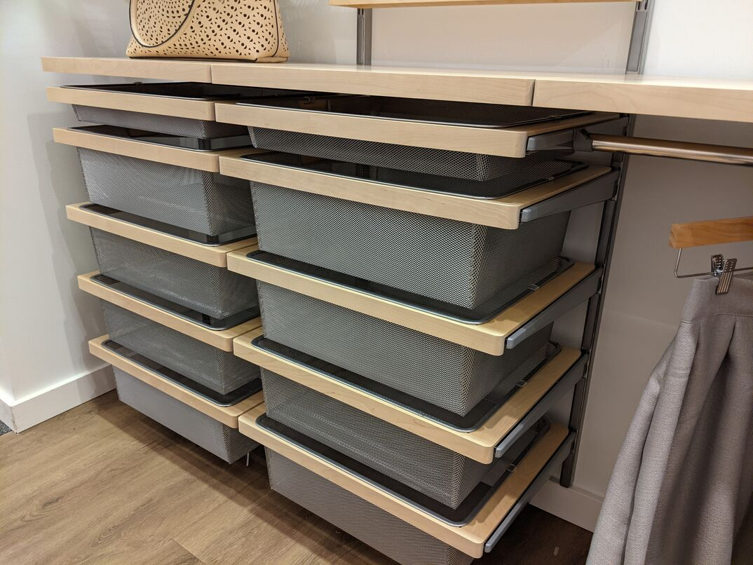 Angled view of a set of wire mesh drawers inside a large walk in closet