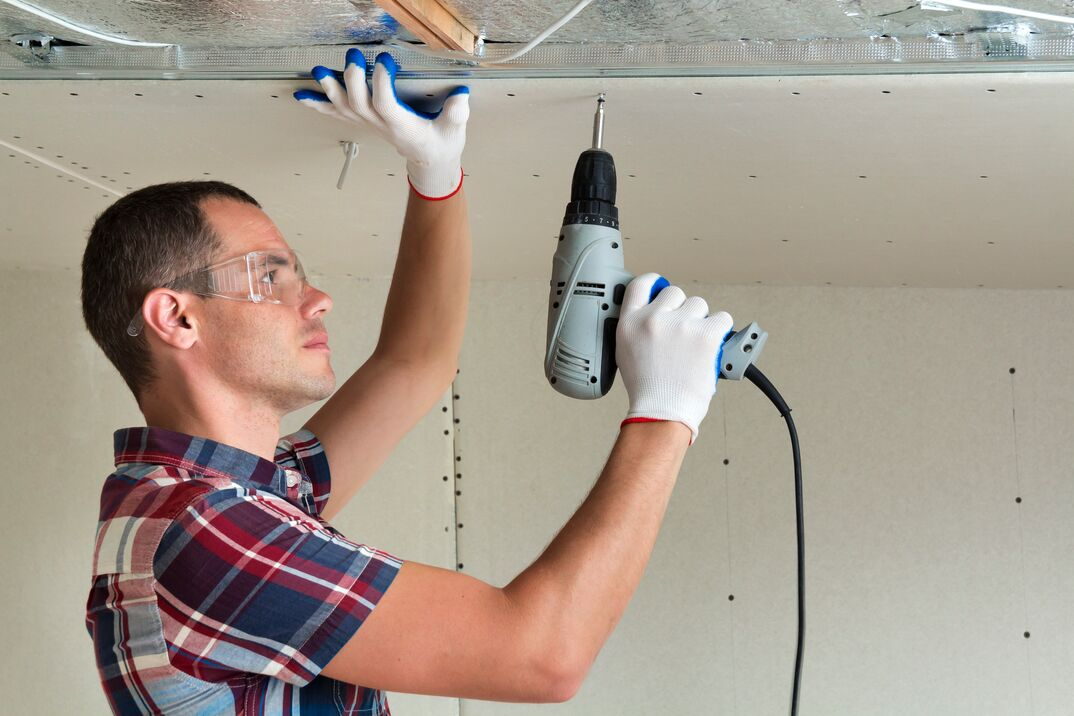 Man in goggles hangs drywall on the ceiling to metal frame using electrical screwdriver