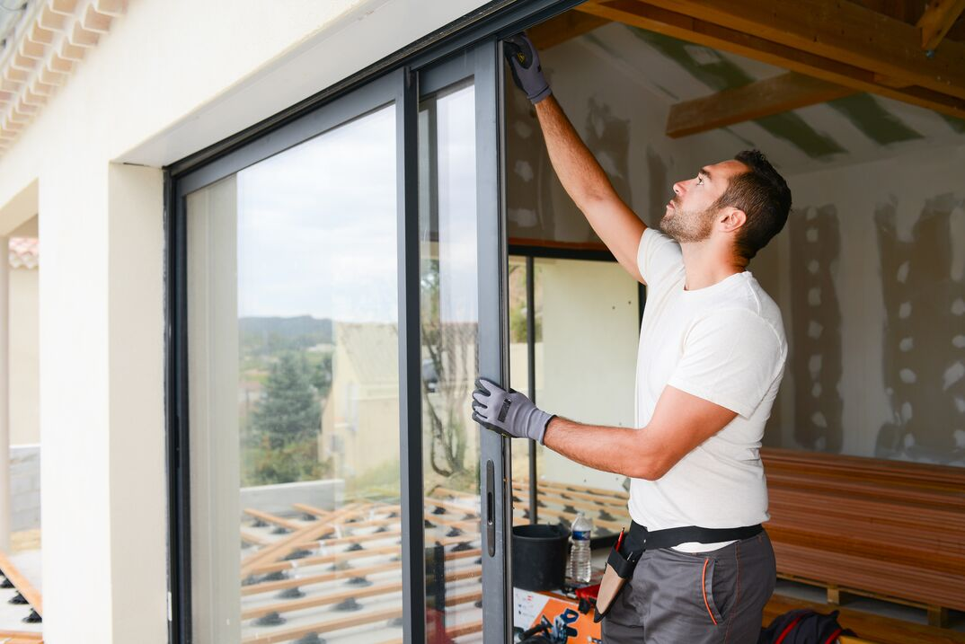 a male contractor wearing black work gloves installing a sliding glass door into a new home