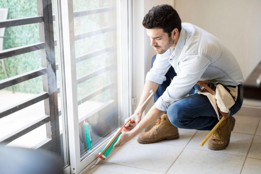 a male contractor applies caulk or sealant along the base of a sliding glass door