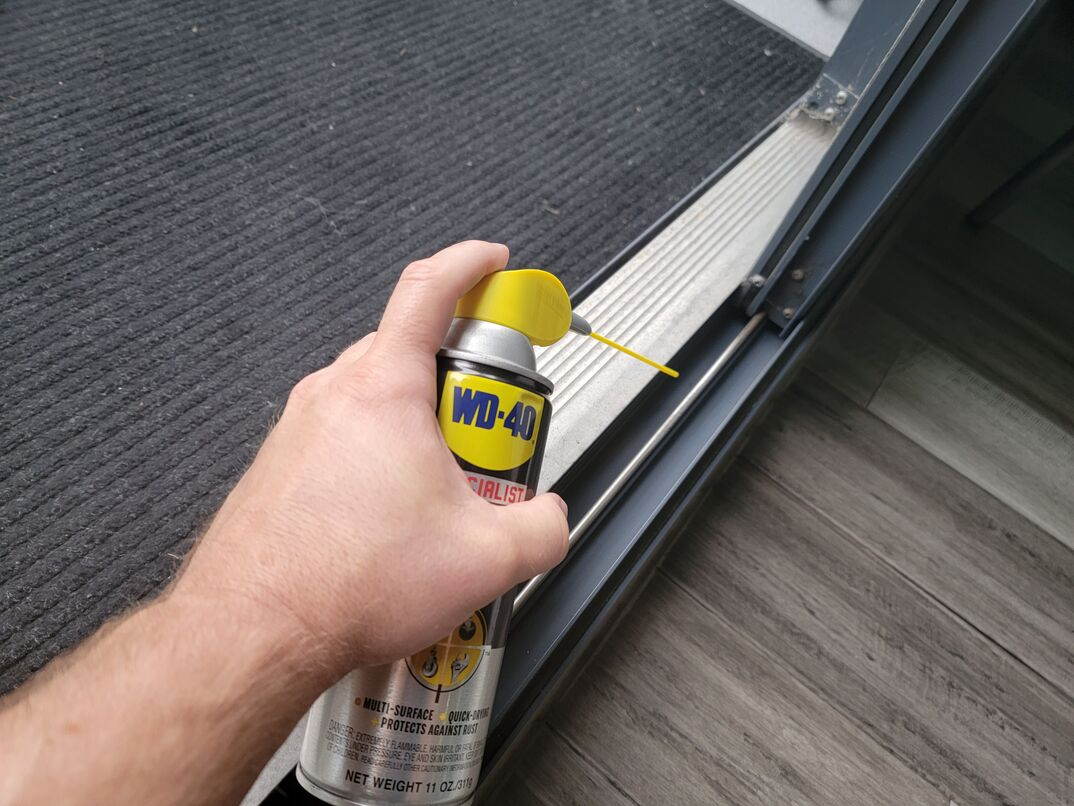 Human hand using WD-40 to lubricate sliding glass door track.