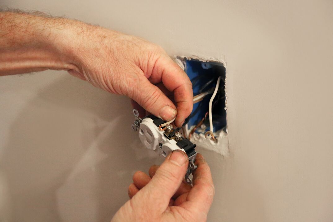 electrician fixing electrical outlet