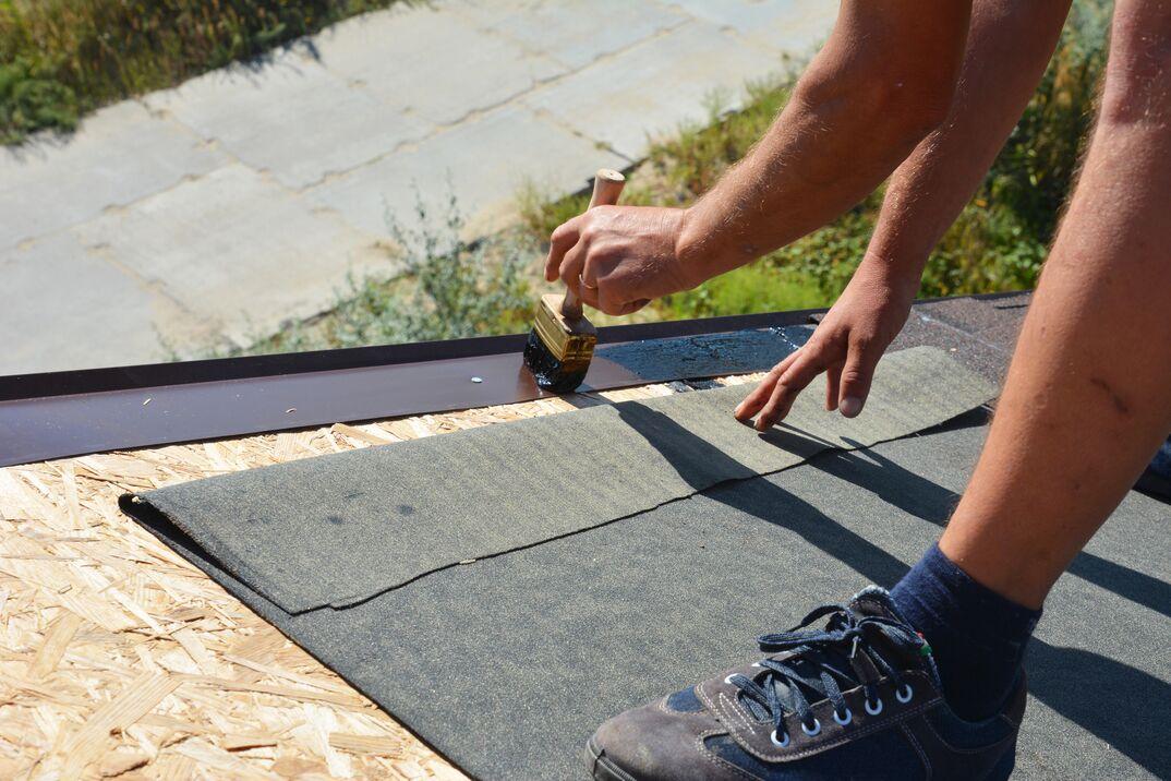 A building contractor is installing underlayment
