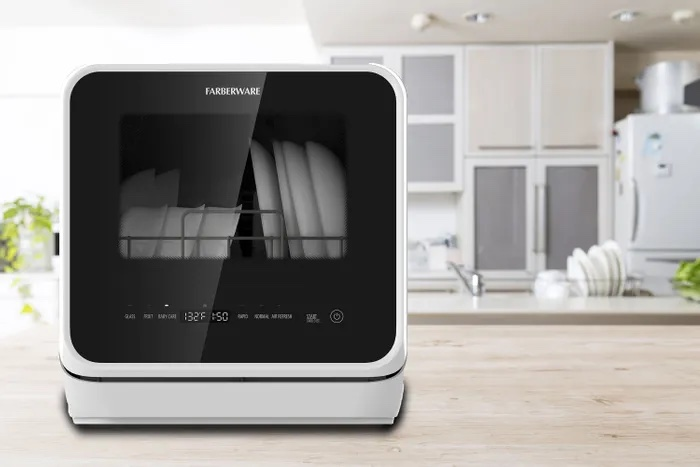 Photo of a  faberware  branded countertop dishwasher sitting on a modern countertop with a white modern kitchen in the background  This image is media supplied