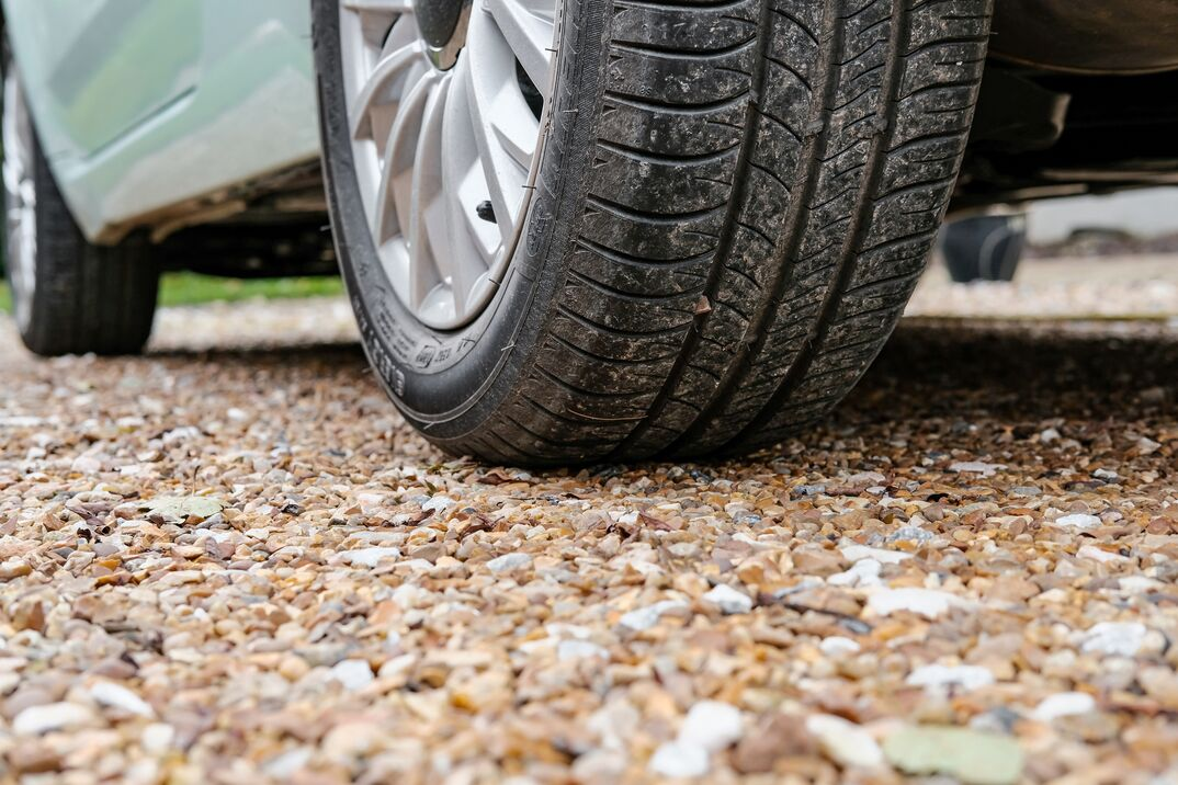 close up of a vehicle s tire parked on a gravel driveway
