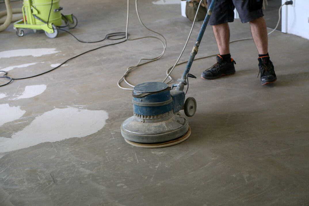 Worker grinding the floor using a single disc machine
