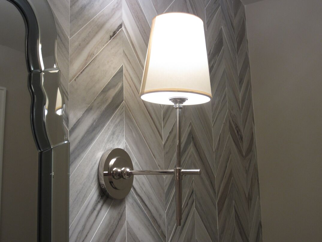 Mounted sconce on a tile wall in the bathroom