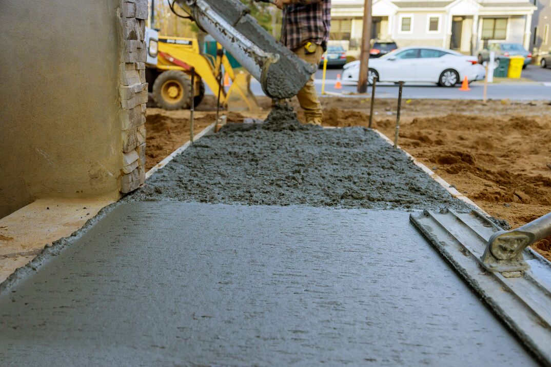 Construction worker pour cement for sidewalk in new residential home