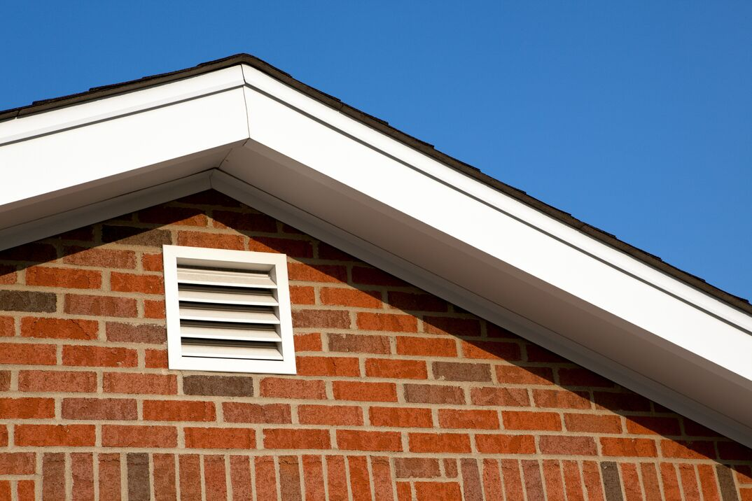 a white gable vent sits under a roof overhand on a brick home