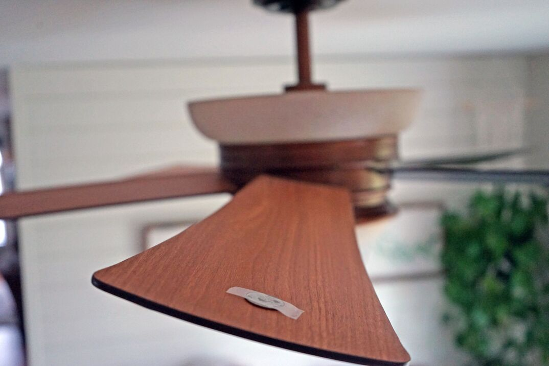 a quarter coin taped to the blade of a wooden ceiling fan to add balance