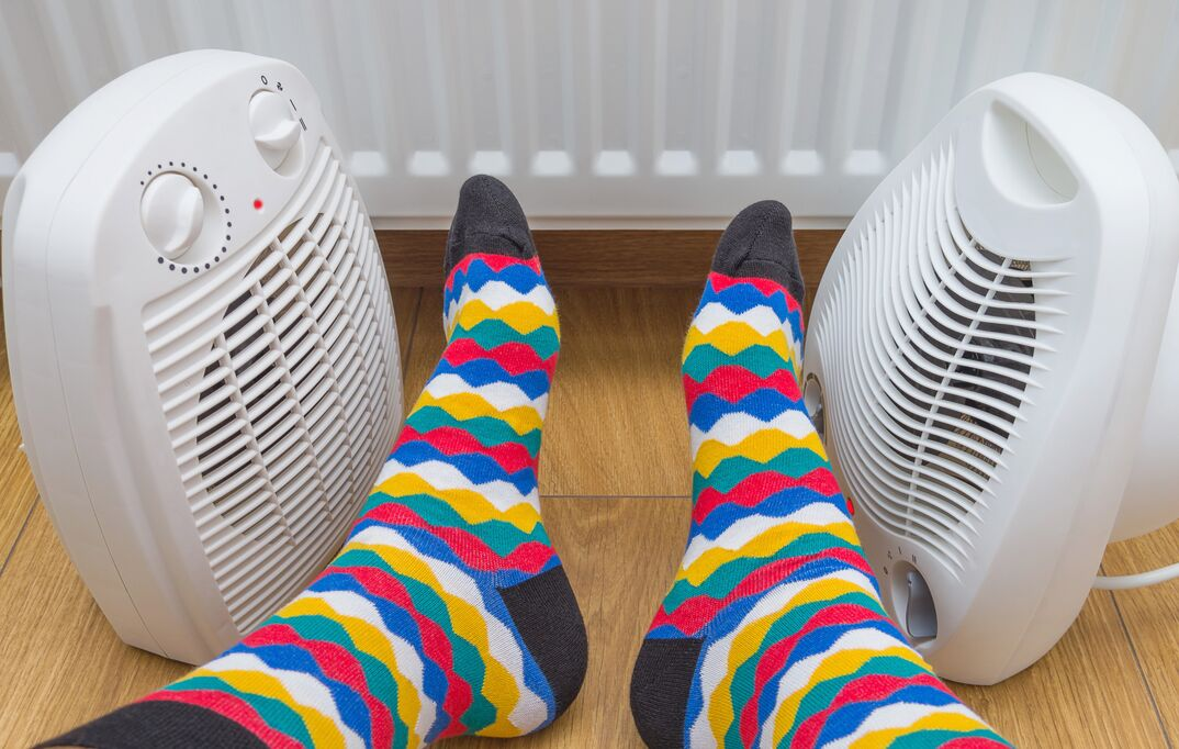 A pair of household space heaters warming a pair of feet