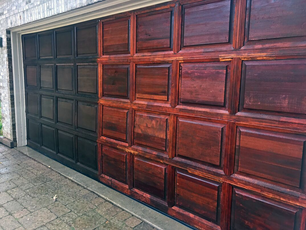 Aged red oak garage door getting power washed and refinished.